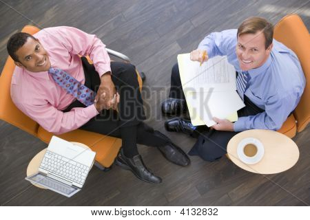 Two Businessmen Sitting Indoors With Coffee Laptop And Folder Smiling