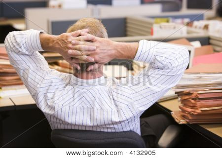 Businessman In Cubicle With Stacks Of Files