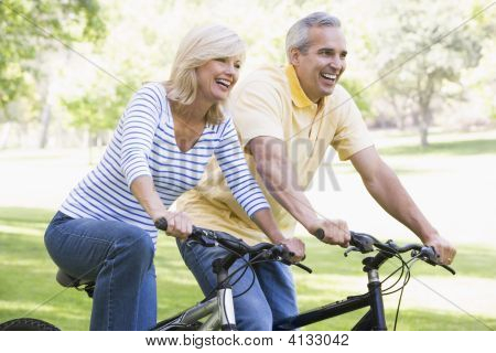 Couples On Bikes Outdoors Smiling