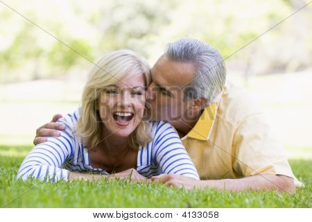 Couples Relaxing Outdoors In Park Kissing And Smiling