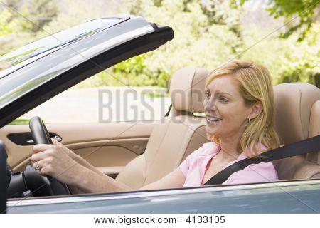 Mujer en coche descapotable sonriendo
