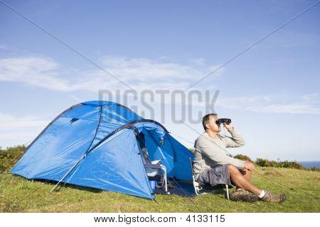 Man Camping Outdoors And Looking Through Binoculars