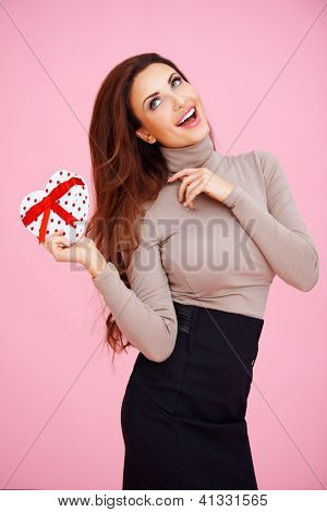 Romantic beautiful laughing woman with a heart shaped Valentine gift in her hand on a pink studio background