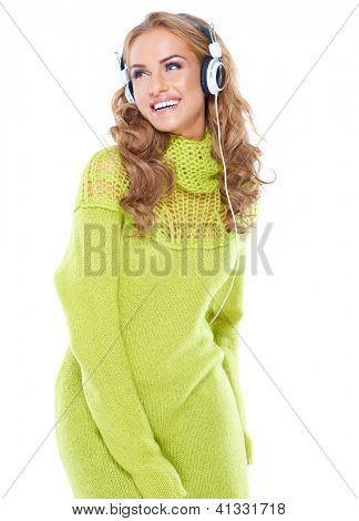 Happy woman with long curly blonde hair enjoying her music laughing over her shoulder as she sways to the rythm isolated on white