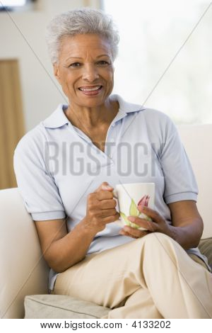 Woman sitting in Living Room with Kaffee lächelnd
