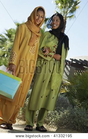 Low angle view of two female friends standing together with shopping bags