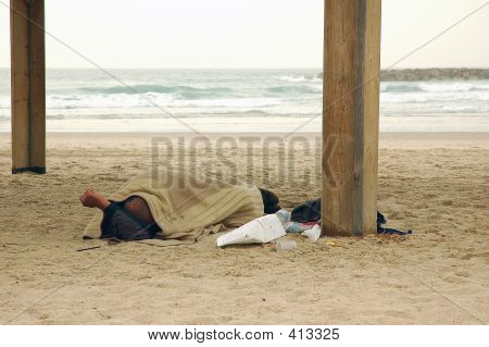 Homeless Person Sleeping On Beach