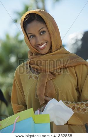 Portrait of a happy Indian woman holding shopping bags