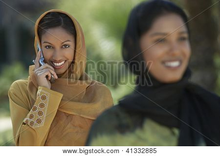 Portrait of a happy beautiful woman on a call with friend in the foreground