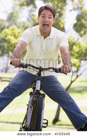 Man Outdoors On Bike With Legs Out