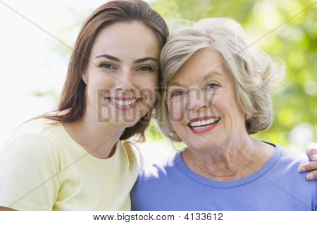 Two Women Outdoors Embracing And Smiling