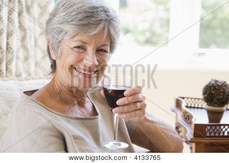 Frau im Wohnzimmer mit Glas Wein lächelnd