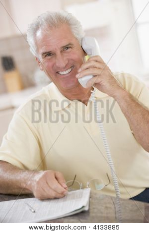 Man In Kitchen On Telephone Smiling