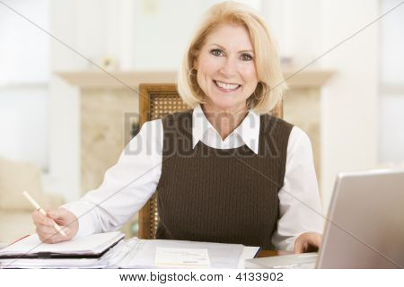 Woman In Dining Room With Laptop And Paperwork Smiling