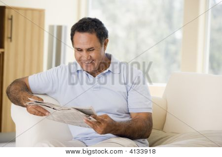 Man Relaxing With Newspaper In Living Room And Smiling