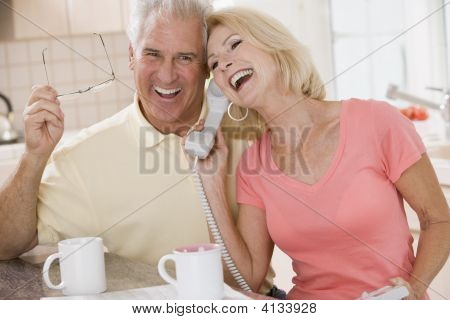 Couples In Kitchen Using Telephone Together And Laughing