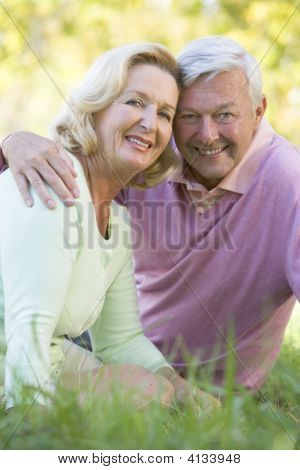 Couples Relaxing In Park Smiling