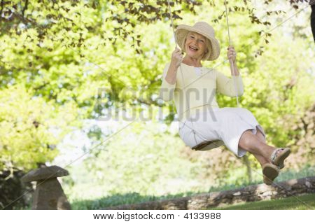 Woman In A Swing Outdoors Smiling