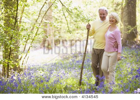 Couples Walking Outdoors With Walking Stick Smiling