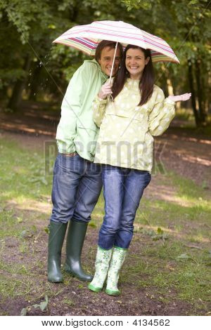 Couples Outdoors In Rain With Umbrella Smiling
