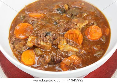 A serving bowl full of freshly home-made oxtail stew, a delicious traditional British or European food.