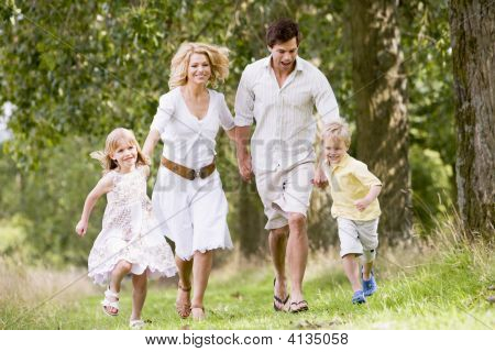 Families Running On Path Holding Hands Smiling