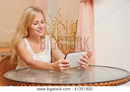Young smiling woman in the cafe with tablet PC