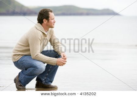 Man Crouching On Beach