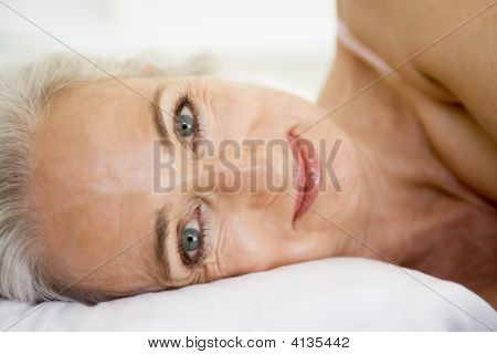 Frau liegend im Bett lächelnd