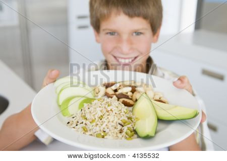 Young Boy In Kitchen Eating Rice Fruit And Nuts Smiling