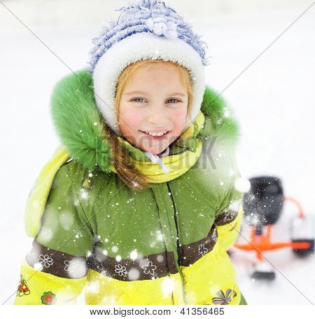Portrait of Happy litte girl with children's snowmobile