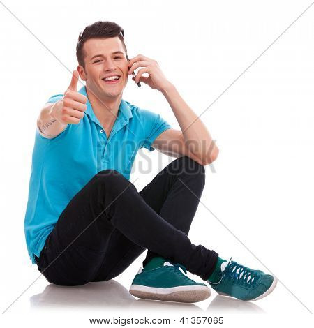 Appealing casual young man sitting with his legs crossed and showing thumbs up sign, while speaking on the phone and smiling to the camera. Isolated on white background