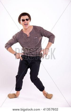 funny young casual man is fooling around, playing cripple, on a light background