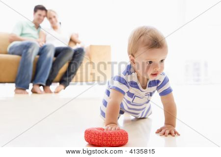 Couples In Living Room With Baby Smiling
