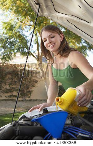 Hermosa joven aceitar el motor del coche