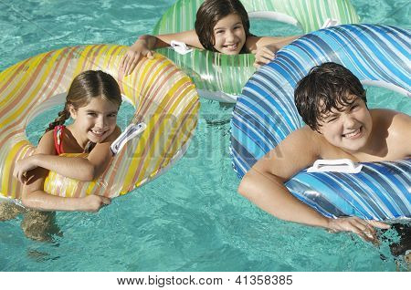 Portrait of a three Caucasian friends enjoying together in swimming pool