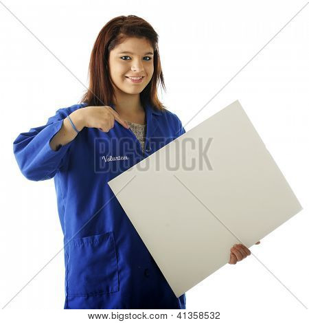 An attractive young volunteer happily pointing to the blank sign (for your text) that she hold.  On a white background.