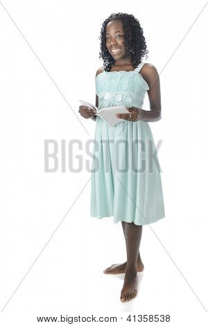A beautiful African American preteen happily looking up from the opened white Bible she holds in her hands.  She's standing barefoot in her sundress.  On a white background.