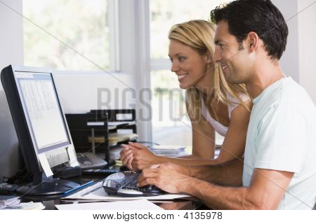 Couples In Home Office Using Computer And Smiling