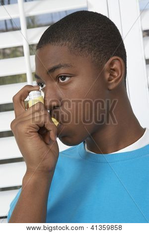 Young African American boy using asthma inhaler