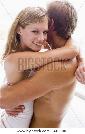 Couples Embracing In Bedroom Smiling