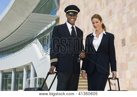 Portrait of happy pilot and air hostess standing together with luggage at the airport