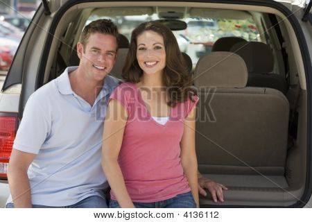 Couples Sitting In Back Of Van Smiling