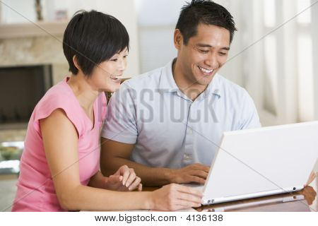 Couples In Dining Room With Laptop Smiling