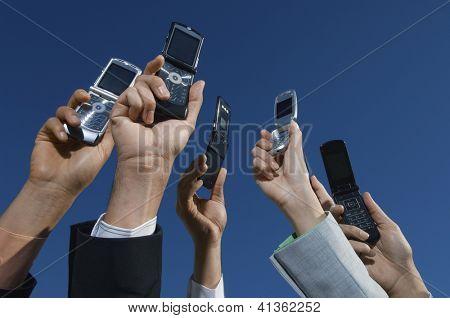Recorta la imagen de manos de multi étnica empresarios sostener teléfonos móviles contra el cielo azul
