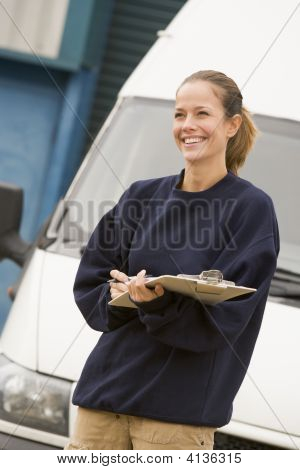 Deliveryperson Standing With Van Writing In Clipboard Smiling