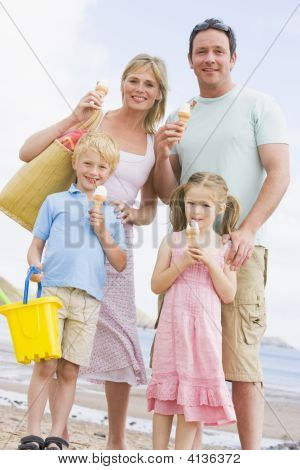 Families Standing At Beach With Ice Cream Smiling