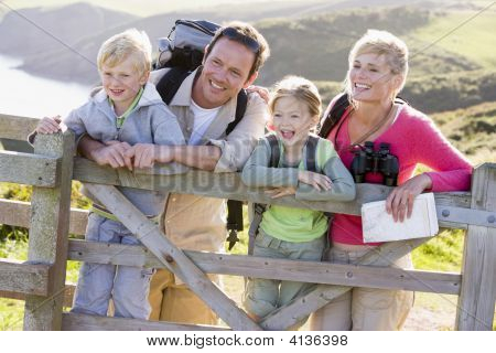Families On Cliffside Path Leaning On Fence And Smiling
