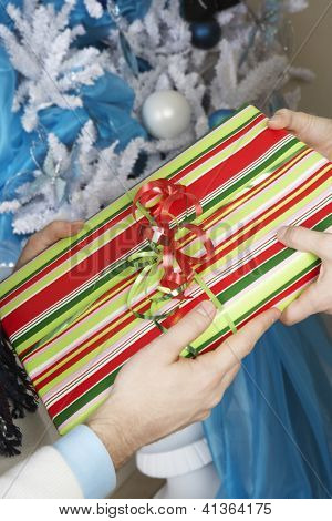 Close up of hands exchanging gift box with Christmas tree in the background