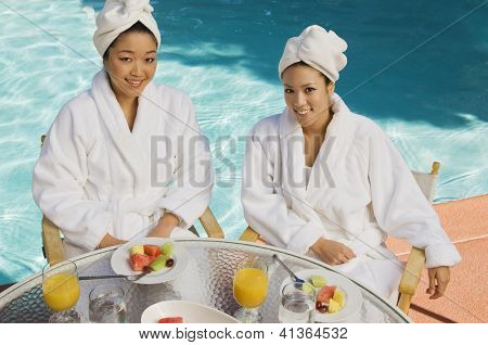 High angle view of two female friends having breakfast together by the pool side